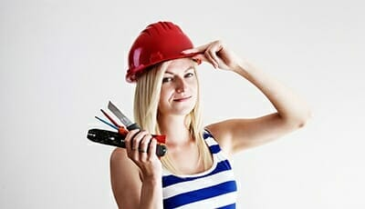woman holding tools and a helmet