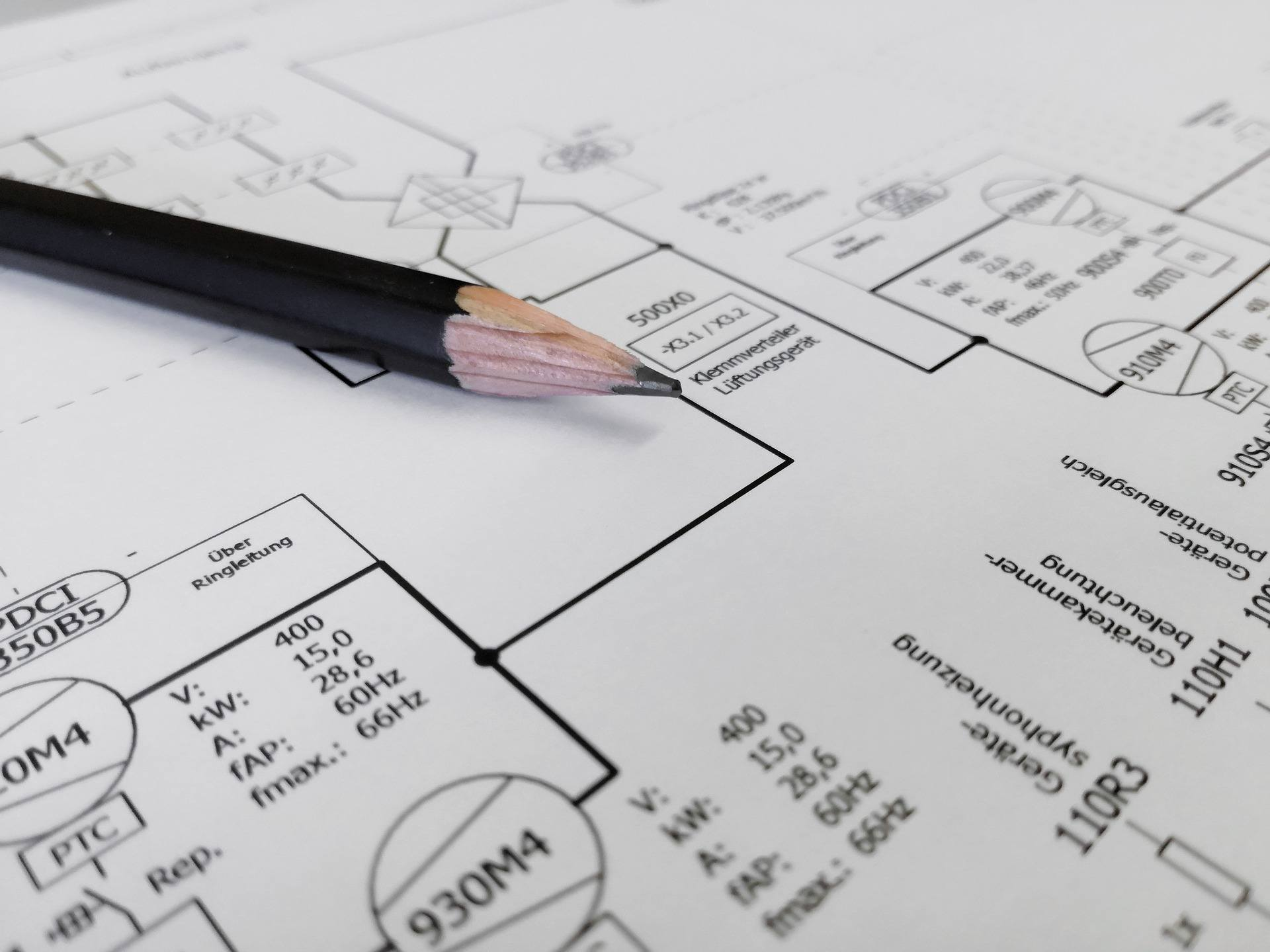 pen on top of electrical blueprints